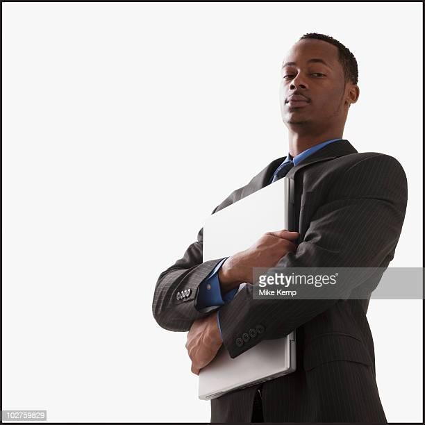Serious businessman holding a laptop computer