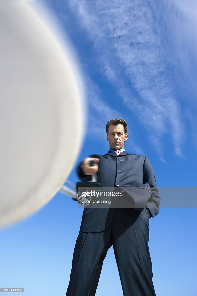 Serious Businessman Holding a Satellite Dish : Stock Photo