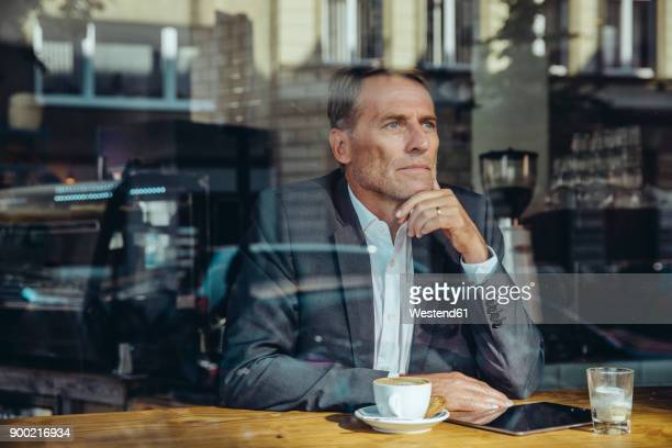 Serious businessman in cafe looking out of window
