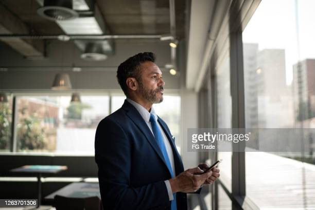 serious businessman looking through the window - latin american and hispanic ethnicity stock pictures, royalty-free photos & images