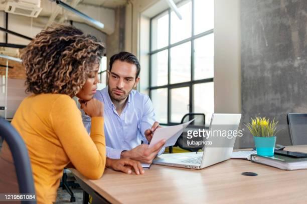 ernstige zakenman die op papierwerk richt dat collectieve software met collega bespreekt - medewerkerbetrokkenheid stockfoto's en -beelden