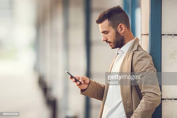 重大なビジネスマンリーティングテキストメッセージを携帯電話ください。