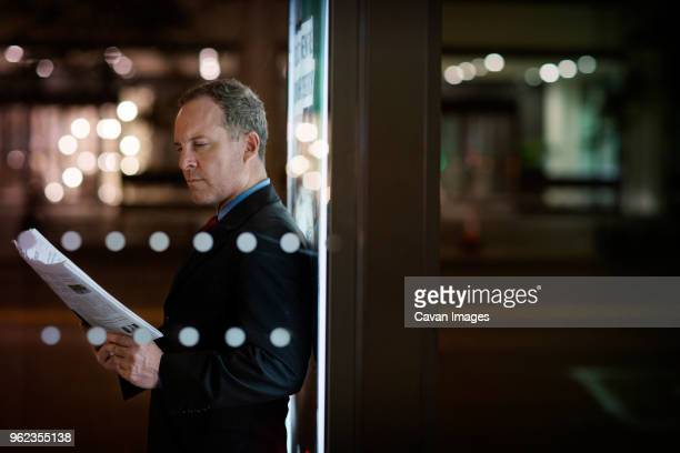 Serious businessman reading newspaper while standing against illuminated poster in city