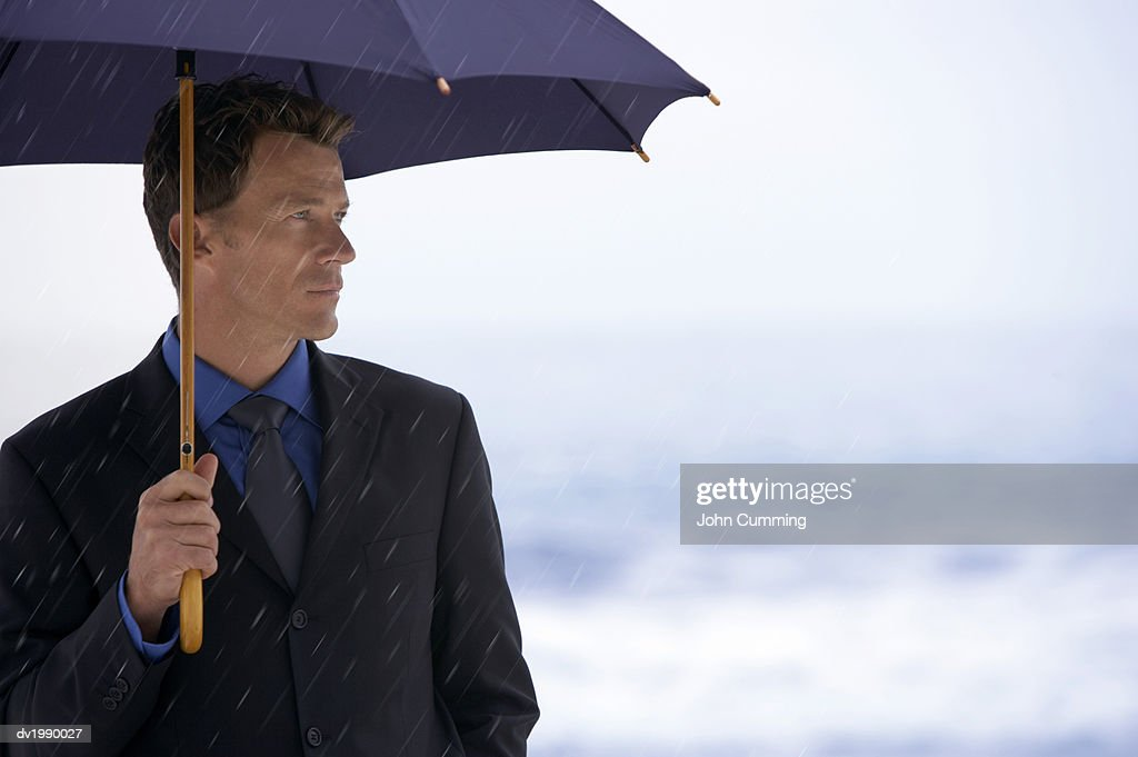 Serious Businessman Sheltering Underneath an Umbrella in the Rain : Stock Photo