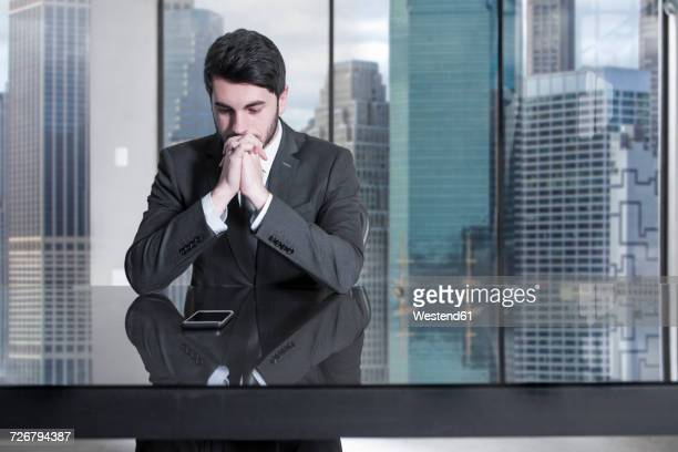 Serious businessman sitting at desk in city office looking at cell phone
