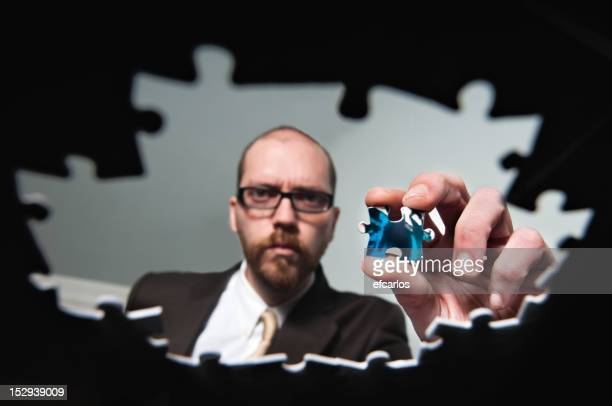 Serious businessman solving problems on a puzzle