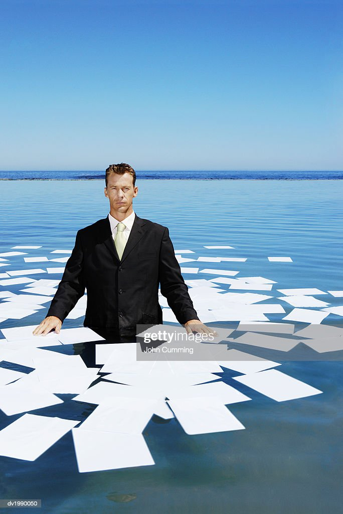 Serious Businessman Standing in the Sea, with Paperwork Floating Around Him : Stock Photo