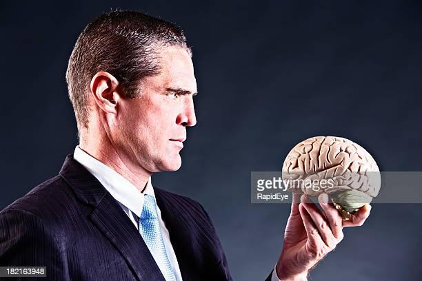 Serious businessman studies model brain