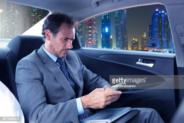 Serious businessman traveling in car and using smart phone