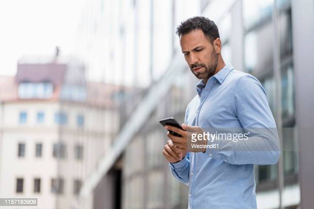 serious businessman using cell phone in the city - wut stock-fotos und bilder