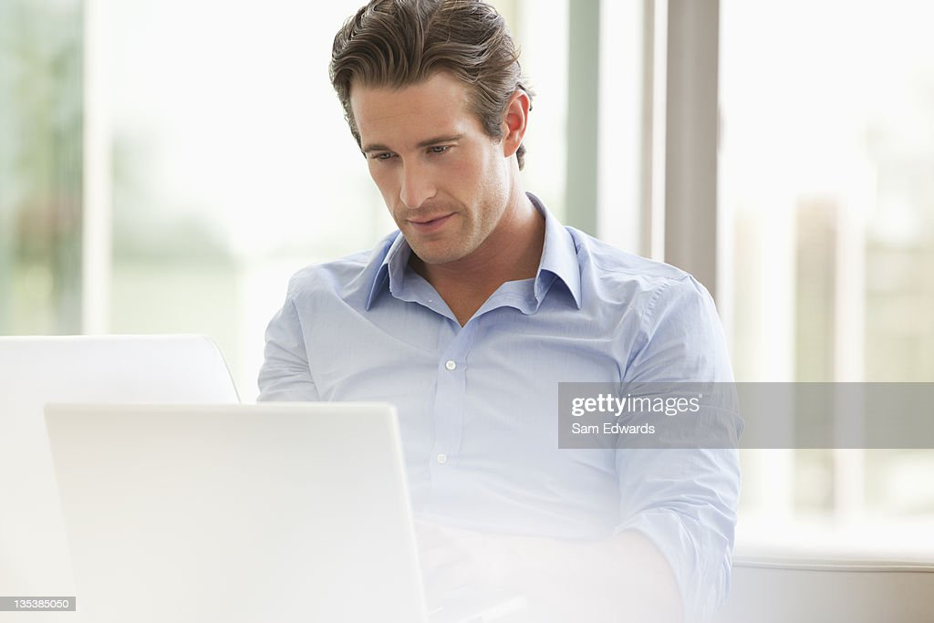 Serious businessman using laptop : Stock Photo