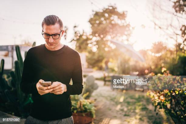 serious businessman using mobile phone while standing against plants on sunny day - long sleeved stock photos and pictures
