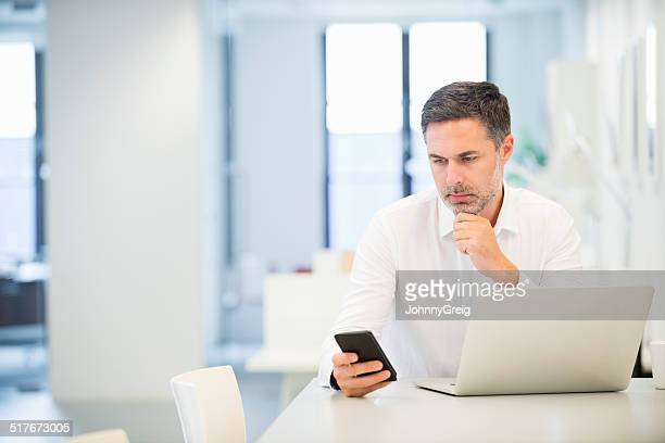 Serious Businessman Using Smart Phone In Office