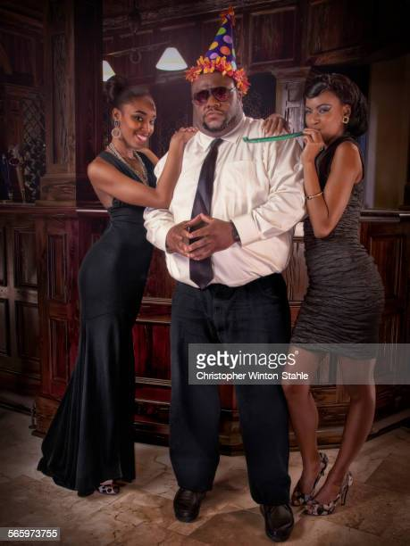 Serious businessman wearing party hat celebrating with women