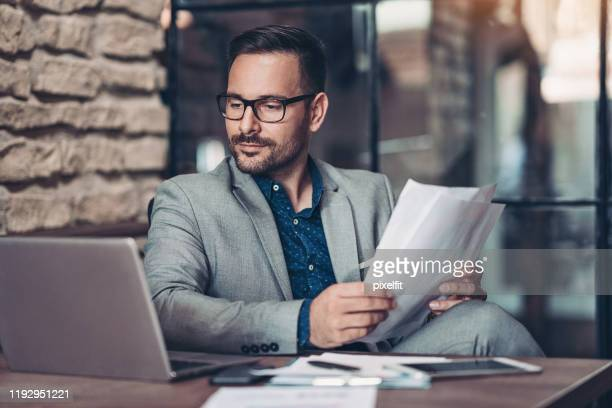 serious businessman with laptop and documents - executive director stock pictures, royalty-free photos & images