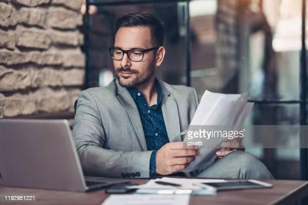 ラップトップとドキュメントを持つ深刻なビジネスマン - エグゼクティブディレクター ストックフォトと画像