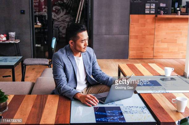 serious businessman working on laptop - asian stock pictures, royalty-free photos & images