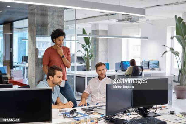serious businessmen looking at computer in office - cloud computing stock photos and pictures