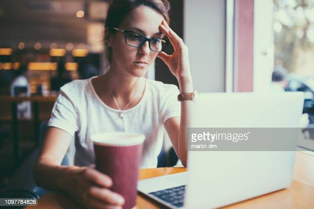 serious businesswoman in cafe reading the online news in politics - news event stock pictures, royalty-free photos & images