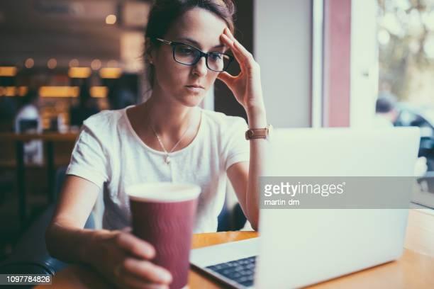 empresaria seria en café leyendo las noticias en línea en la política - crisis fotografías e imágenes de stock