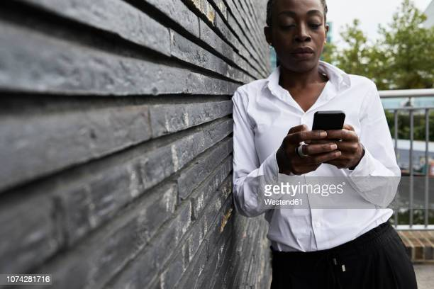 Serious businesswoman leaning against wall looking at smartphone