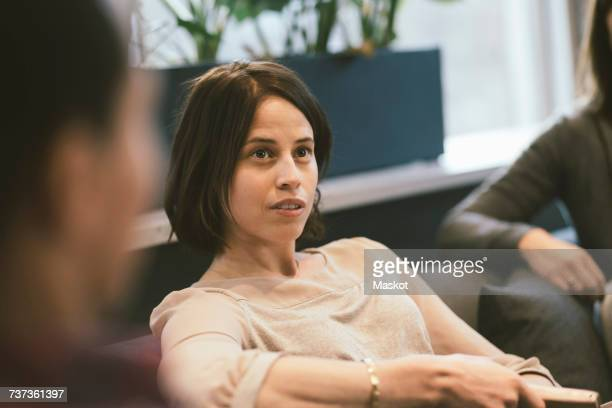 serious businesswoman listening in meeting at office - kleine groep mensen stockfoto's en -beelden