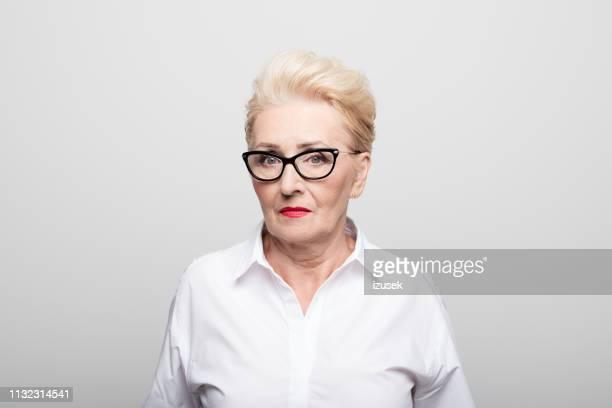 femme d'affaires sérieuse sur le fond blanc - formal portrait photos et images de collection