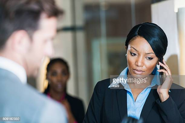 Serious businesswoman talking on mobile phone in office