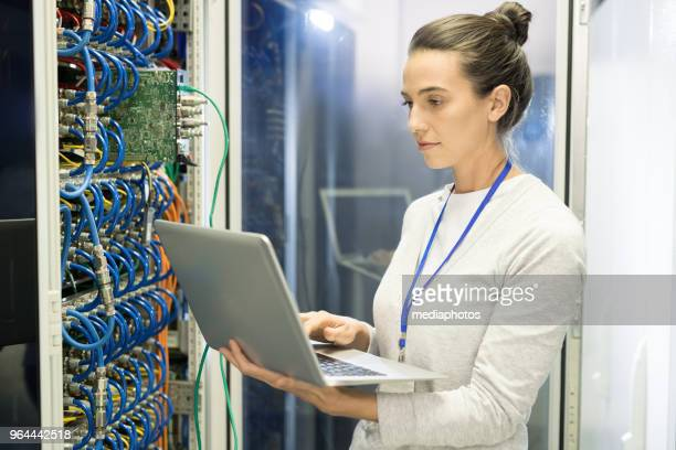 serious busy female technical engineer with badge adjusting equipment of supercomputer by means of laptop in network server room - server room stock pictures, royalty-free photos & images