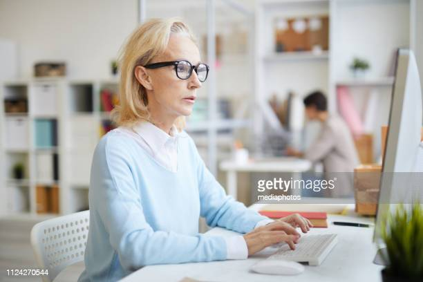 Serious busy mature business lady in glasses sitting at table and typing on computer while working on online project in modern office