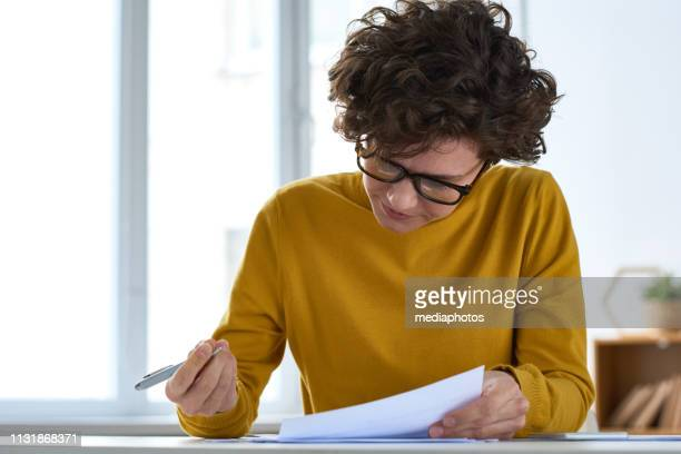 serious busy young lady with short curly hair sitting at desk and filling document while preparing tax papers - signing stock pictures, royalty-free photos & images
