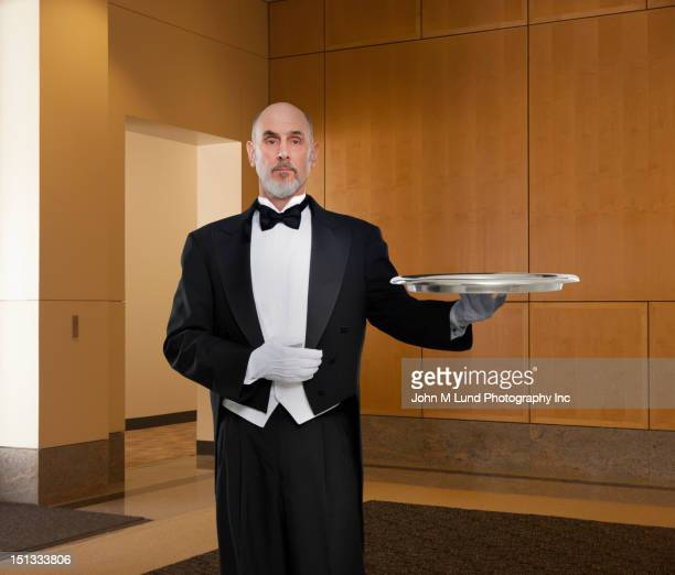 serious butler holding tray - waiter stock pictures, royalty-free photos & images