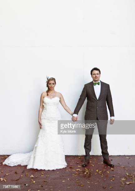 Serious Caucasian bride and groom holding hands