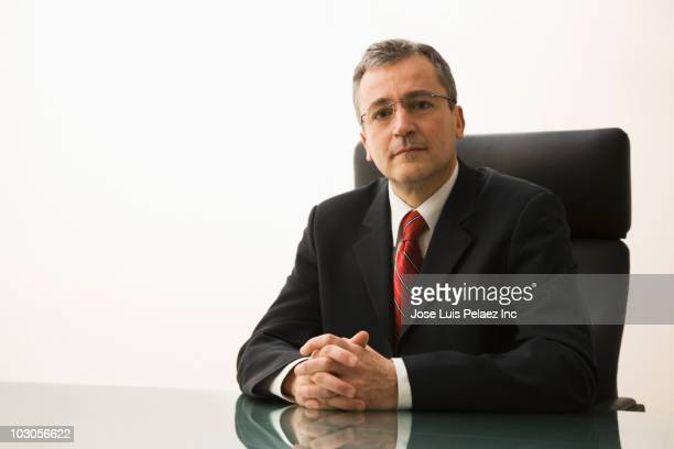 Serious Caucasian businessman sitting at desk