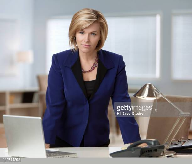 Serious Caucasian businesswoman leaning on desk