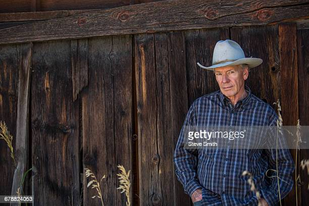Serious Caucasian farmer leaning on wooden fence