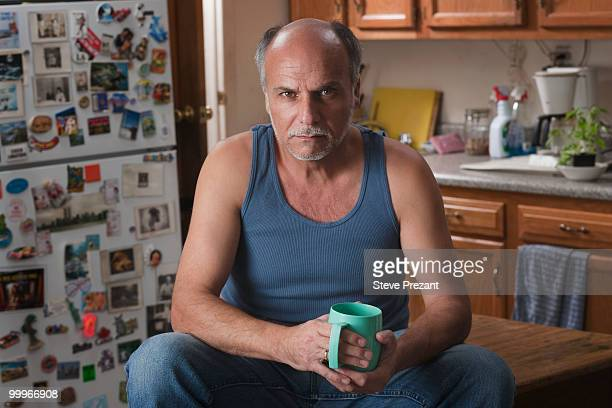Serious Caucasian man drinking coffee in kitchen