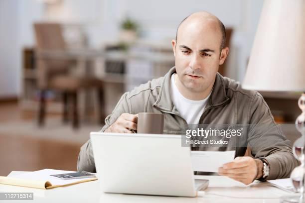 sérieux homme caucasien payant les factures - un seul homme d'âge moyen photos et images de collection