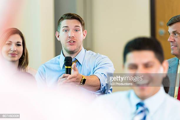 serious caucasian man questions a candidate during town hall meeting - town hall meeting stock photos and pictures