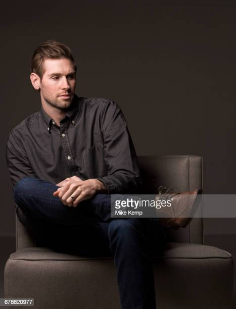 Serious Caucasian man sitting in armchair