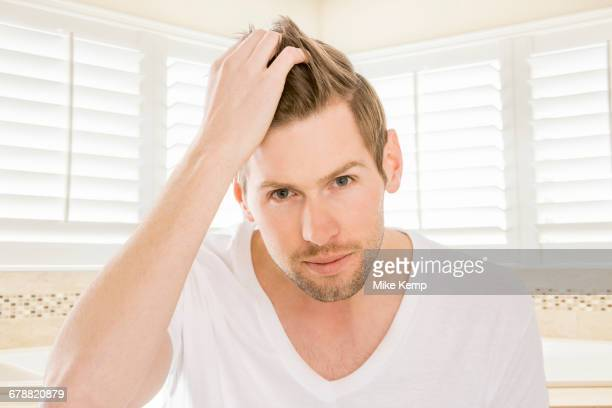 Serious Caucasian man styling hair in bathroom
