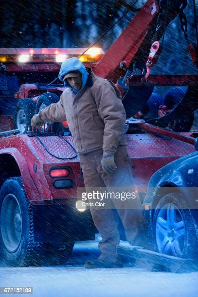 Serious Caucasian tow truck driver towing car