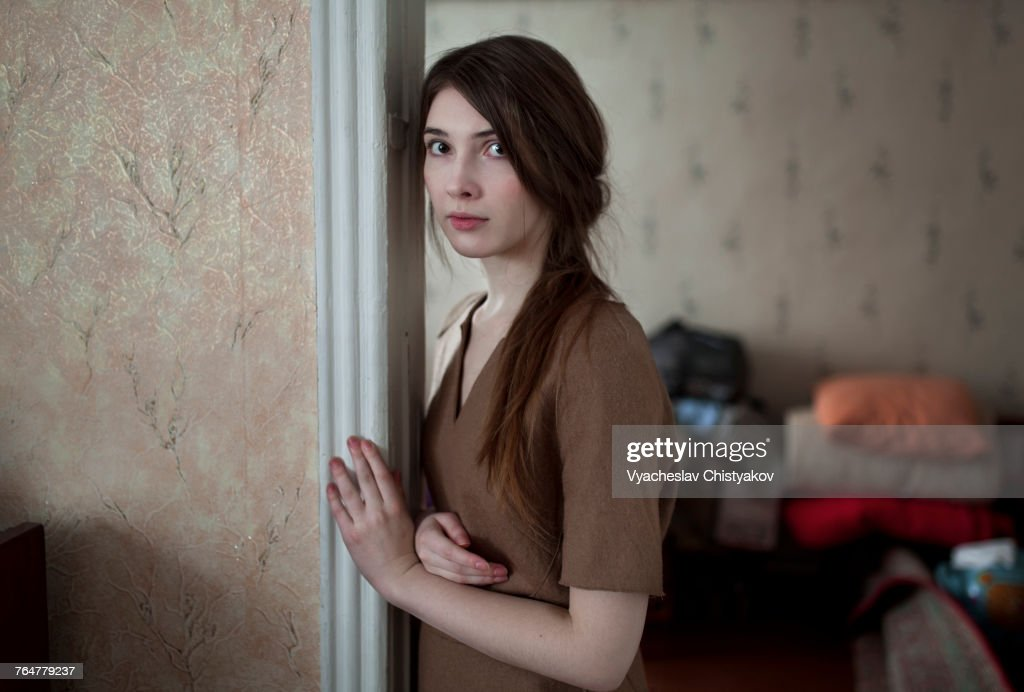 Serious Caucasian woman leaning in doorway : Stock Photo