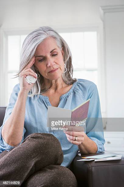 Serious Caucasian woman reading card on sofa