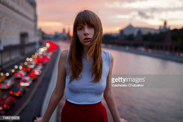 Serious Caucasian woman standing at urban waterfront