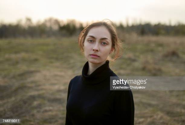 Serious Caucasian woman standing in field