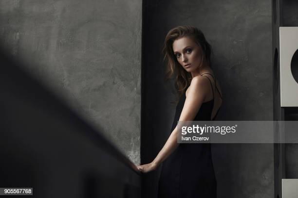 serious caucasian woman standing near wall - mirar por encima del hombro fotografías e imágenes de stock