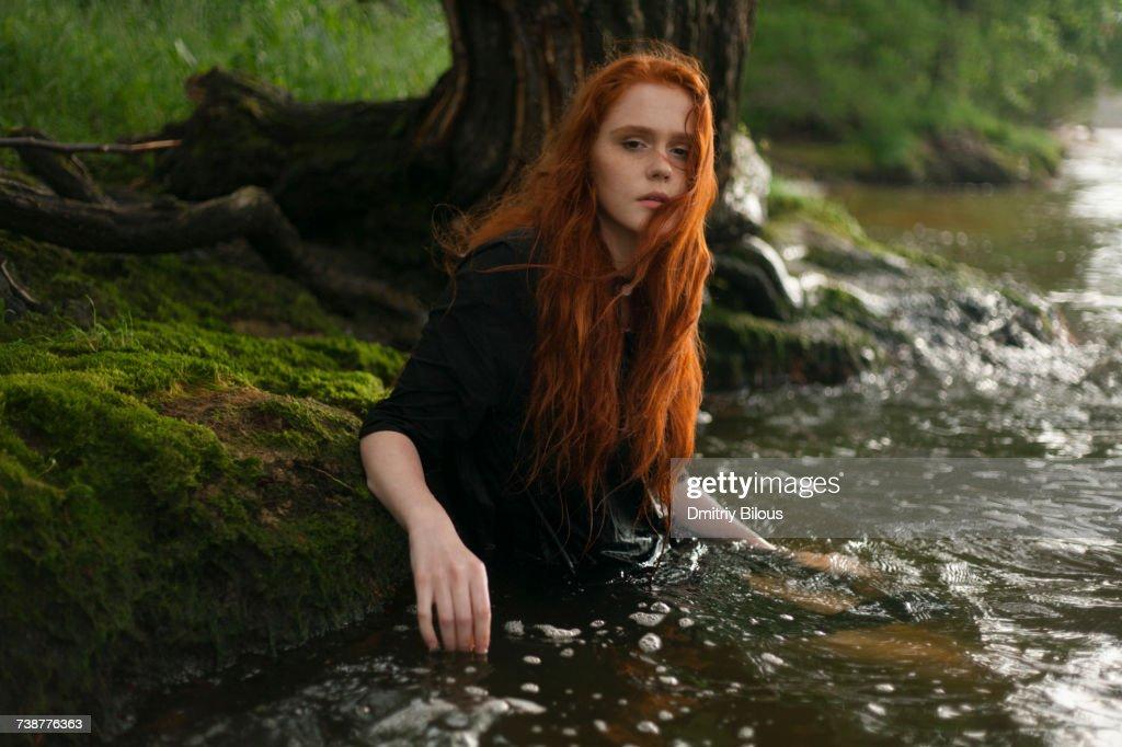 Serious Caucasian woman standing waist deep in water : Stock Photo