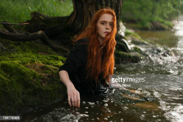 serious caucasian woman standing waist deep in water - lake auburn stock photos and pictures
