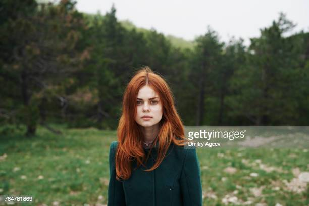 serious caucasian woman wearing coat in field - redhead stock pictures, royalty-free photos & images